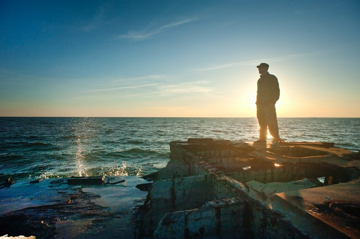 silhouette photo of man standing near the edge of concrete 1060492